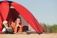 Kamperende gelukkige vrouw in tent op strand Royalty-vrije Stock Foto's