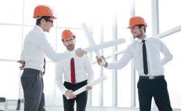 Kampf mit drei Architekten mit beschränkten Bauplänen stockbilder