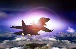 Kampfflugzeugfliegen, das Sonnenuntergang gegenüberstellt Stockfoto
