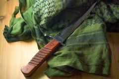 Kampfmesser mit einem Holzgriff, grünes shemagh stockfotografie