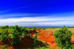 Kampgräsplan och röd under-blå himmel. Royaltyfri Fotografi