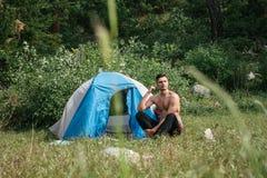 Kampieren in den Bergen Ein Mann sitzt nahe Zelt gegen den Hintergrund von grünen Bäumen und von Bergen Stockfoto