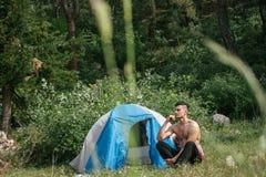 Kampieren in den Bergen Ein Mann sitzt nahe Zelt gegen den Hintergrund von grünen Bäumen und von Bergen Lizenzfreies Stockbild
