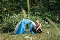Kampieren in den Bergen Ein Mann sitzt nahe Zelt gegen den Hintergrund von grünen Bäumen und von Bergen Lizenzfreies Stockfoto