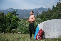 Kampieren in den Bergen Ein Mannstand nahe Zelt gegen den Hintergrund von grünen Bäumen und von Bergen Stockfotos