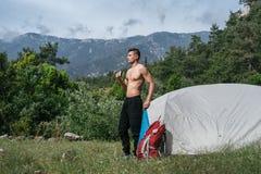 Kampieren in den Bergen Ein Mannstand nahe Zelt gegen den Hintergrund von grünen Bäumen und von Bergen Lizenzfreie Stockbilder