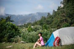 Kampieren in den Bergen Eine Frau sitzt nahe Zelt gegen den Hintergrund von grünen Bäumen und von Bergen Lizenzfreie Stockbilder