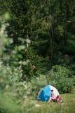Kampieren in den Bergen Eine Frau sitzt nahe Zelt gegen den Hintergrund von grünen Bäumen und von Bergen Lizenzfreie Stockfotografie