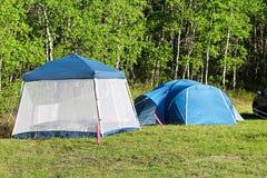 Kampieren mit einem Zelt und Haben eines Wanzenschirmes, zu zurückzuziehen stockbild