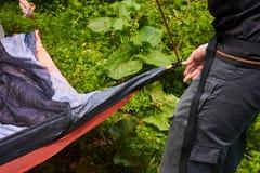 Kampieren Sie im Zelt - der Tourist, der ein Zelt auf dem Kampieren einstellt Abschluss herauf Mann ` s Hände halten ein Zelt bei Stockfoto