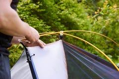 Kampieren Sie im Zelt - der Tourist, der ein Zelt auf dem Kampieren einstellt Abschluss herauf Mann ` s Hände halten ein Zelt bei Lizenzfreie Stockbilder