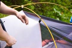 Kampieren Sie im Zelt - der Tourist, der ein Zelt auf dem Kampieren einstellt Abschluss herauf Mann ` s Hände halten ein Zelt bei Stockbild