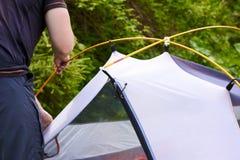 Kampieren Sie im Zelt - der Tourist, der ein Zelt auf dem Kampieren einstellt Abschluss herauf Mann ` s Hände halten ein Zelt bei Lizenzfreie Stockfotografie