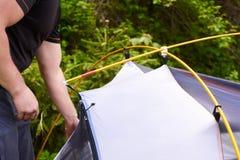 Kampieren Sie im Zelt - der Tourist, der ein Zelt auf dem Kampieren einstellt Abschluss herauf Mann ` s Hände halten ein Zelt bei Stockbilder