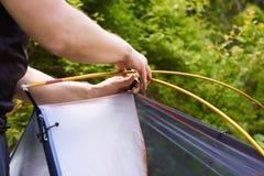 Kampieren Sie im Zelt - der Tourist, der ein Zelt auf dem Kampieren einstellt Abschluss herauf Mann ` s Hände halten auf die Ober Lizenzfreies Stockbild