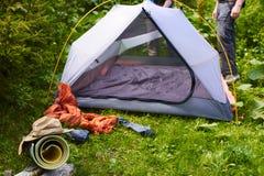 Kampieren Sie im Zelt - die Touristen, die ein Zelt auf dem Kampieren einstellen Stockfotografie