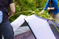 Kampieren Sie im Zelt - die Touristen, die ein Zelt auf dem Kampieren einstellen Abschluss herauf Mann ` s Hände halten ein Zelt  Lizenzfreies Stockbild