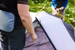 Kampieren Sie im Zelt - die Touristen, die ein Zelt auf dem Kampieren einstellen Abschluss herauf Mann ` s Hände halten ein Zelt  Lizenzfreies Stockfoto