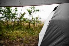 Kampieren am Strand bei Regen und schlechtem Wetter in Schweden mit einem grauen Zelt und einer Plane Stockfoto