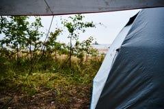 Kampieren am Strand bei Regen und schlechtem Wetter in Schweden mit einem grauen Zelt und einer Plane Lizenzfreie Stockfotografie