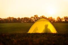 Kampieren und Reisen, Zelt mit den Schattenbildern einer Frau und ihr Hund stockbilder