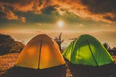 Kampieren und Zelte auf hohem Boden mit Sonnenaufgangsonnenuntergang stockfotografie