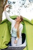 Kampierende Frau Selfie im Zelt, das Selbstporträt unter Verwendung Kamera Smartphone nimmt lizenzfreie stockfotos