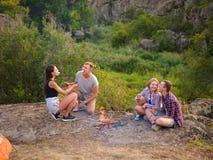 Kampierende Studenten nähern sich Feuer auf einem natürlichen Hintergrund Nette Paare, die Eibische essen Picknicktageskonzept Ko stockbild