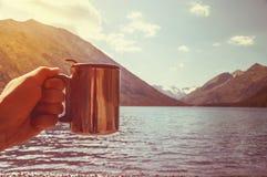 Kampierender Becher an einer Seelandschaft Stockbilder
