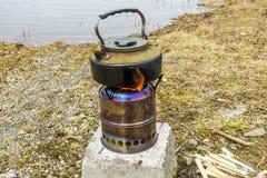 Kampierender Holzgasofen mit einem Kessel stockfoto