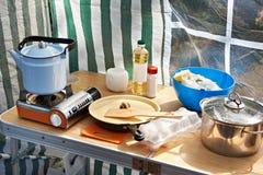 Kampierender Ofen mit Kessel und Tonware auf Tabelle stockfoto
