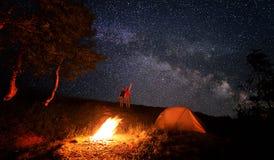 Kampierendes Feuer und Zelt unter dem erstaunlichen sternenklaren Himmel mit Los glänzenden Sternen Stockfoto