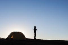 Kampierendes Schattenbild eines Zeltes und des Mädchens im Hoch Stockfotografie