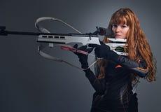 Kampioen die van roodharige de vrouwelijke Biathlon met een concurrerend kanon streven stock fotografie