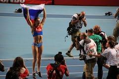 Kampioen E Isinbayeva die met Russische vlag springen royalty-vrije stock afbeeldingen