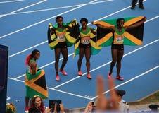 Kampioen Shelly-Ann Fraser-Pryce en anderen met vlaggen Stock Afbeeldingen