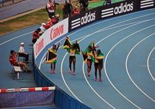 Kampioen Shelly-Ann Fraser-Pryce en anderen met vlaggen Royalty-vrije Stock Fotografie