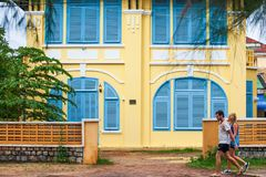 Young couple tourist walking past old french colonial building o. Kampot, Cambodia – SEPTEMBER 22, 2013: Young couple tourist walking past old french colonial Stock Images