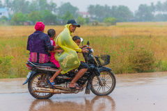 Cambodian family. KAMPOT, CAMBODIA - DECEMBER 14: Cambodian family unidentified rides a scooter foursome two adults, two children while getting wet in heavy rain Royalty Free Stock Photography
