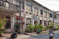 Kampot, Camboja - 12 de abril de 2018: opinião da cidade com construções e a mulher coloniais francesas do khmer no 'trotinette' imagens de stock