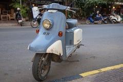 Kampot, Kambodja - 12 April 2018: blauwe uitstekende autoped op stadsstraat Uitstekende fiets op straat Oude de manierautoped van stock foto