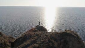 Kampsporter i det härliga landskapet, idrottsman kopplade in Kickboxing på kullen vid havet i ljust solljus på vatten mot himmel lager videofilmer