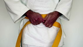 Kampsportkläder, judogi - mannen drar åt hans gula bälte på en vit kimono arkivfilmer