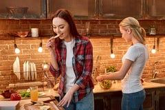Kamratskap är laga mat tillsammans unga kvinnliga vänner i modernt kök som tillsammans förbereder vegetariskt mål cozy arkivbild
