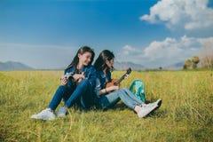 Kamratskap av asiatiskt vila för tonåringkvinnor som är utomhus- arkivfoton