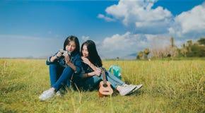 Kamratskap av asiatiskt vila för tonåringkvinnor som är utomhus- fotografering för bildbyråer