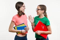 Kamratskap av två tonårs- flickor På en vit bakgrund talar skrattar flickorna och Arkivfoton