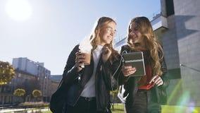 Kamratskap, folk och teknologibegrepp - Lyckliga tonårs- vänner som går och använder minnestavladatordatoren på, parkerar in lager videofilmer