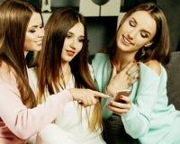 Kamratskap, folk och teknologibegrepp - lyckliga v?nner eller ton?rs- flickor med smartphonen p? hom arkivfoto
