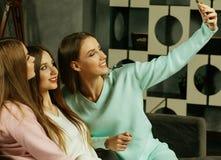 kamratskap, folk och teknologibegrepp - lyckliga v?nner eller ton?rs- flickor med smartphonen som hemma tar selfie royaltyfri bild
